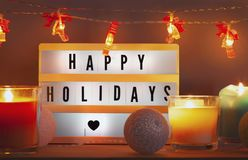 Happy holidays lightbox and Christmas decorations with candles royalty free stock image