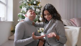 Happy holidays, man and woman catch snow with hands in room sitting on the floor near New Year tree. Happy holidays, man and woman catch snow with hands in the stock video