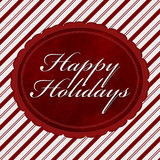 Happy Holidays Message. Red and White Candy Cane Stripe Background with red plush and text Happy Holidays Royalty Free Stock Image