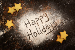 Happy holidays. Message written on the sugar powder with star shaped cakes around Royalty Free Stock Photography