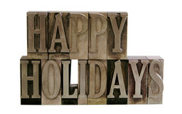 Happy holidays in metal type. The phrase 'Happy Holidays' in letterpress metal letters isolated on white Stock Image