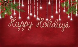 Happy holidays rope design with lights and pine. Happy holidays greeting in rope text on red textured background with glowing string lights and pine bough Royalty Free Stock Photo