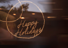 Happy Holidays sign glows. Across a window background around New Years eve Royalty Free Stock Photography