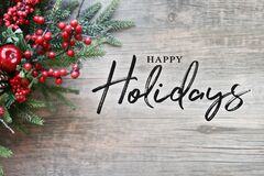 Happy Holidays Text with Christmas Evergreen Branches and Red Winter Holiday Berries in Corner Over Rustic Wooden Background