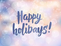 Happy holidays text. Hand drawn greetings quote. Blurred lights background with falling snow and bokeh effect. Happy holidays text. Hand drawn lettering Royalty Free Stock Image
