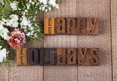 Happy Holidays Text. On a wooden surface with snowy evergreen tree branch and pinecone Stock Photo