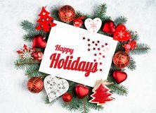 Happy Holidays Text with Holiday Evergreen Branches and photoframe New Year tree, red decorations Top view, flat lay