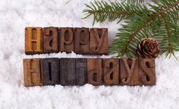Happy Holidays Text. Happy holiday lettering on snowy background with tree branch and pinecone Royalty Free Stock Photography