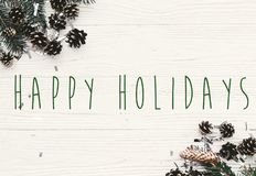 Happy Holidays text on modern christmas flat lay with green fir stock photos