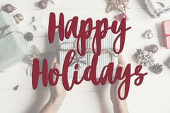 Happy holidays text, seasonal greetings card sign. hands holding Royalty Free Stock Photos
