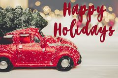 Happy holidays text, seasonal greetings card sign. red car toy w. Ith christmas tree on top on white wood with lights in background Stock Image