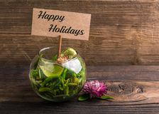 Happy holidays. Text on sign board with flower and leafs on wood Royalty Free Stock Photo