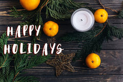 Happy holidays text sign on christmas flat lay wallpaper with gr. Een branches and oranges and golden star on black rustic wooden background. seasonal greeting stock image