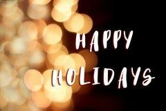 Happy holidays text sign on christmas garland lights at street i. N european city at winter seasonal holidays. decorations outdoors. magic moments. golden bokeh Royalty Free Stock Images
