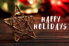 Happy holidays text sign on christmas golden star on background. Of garland lights on black rustic wooden background. space for text. holiday greeting card Stock Photos