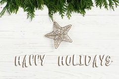 Happy holidays text sign on christmas golden star on green tree. Branches on stylish white rustic wooden background. space for. holiday greeting card concept Stock Photos