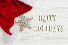 Happy holidays text sign on christmas golden star and santa hat. On white rustic wooden background. space for text. holiday greeting card concept. unusual Royalty Free Stock Photography