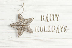 Happy holidays text sign on christmas golden star on stylish whi. Te rustic wooden background. space for text. holiday greeting card concept. unusual creative Royalty Free Stock Images
