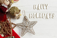 Happy holidays text sign on christmas golden star and toys and r. Ed stockings on white rustic wooden background. space for text. holiday greeting card concept Stock Photos