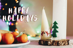 Happy holidays text sign on  christmas rustic table with candle Stock Photography