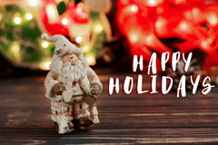 Happy holidays text sign on christmas santa claus toy on backgro. Und of garland lights on black rustic wooden background. space for text. holiday greeting card Royalty Free Stock Photography