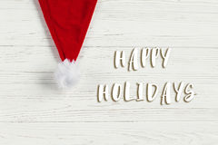 Happy holidays text sign on christmas santa hat on white rustic. Wooden background. space for text. holiday greeting card concept. unusual creative view Stock Photos