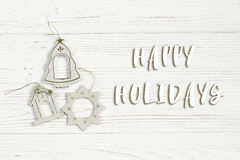 Happy holidays text sign on christmas simple vintage toys on sty. Lish white rustic wooden background. space for text. holiday greeting card concept. unusual Stock Photography