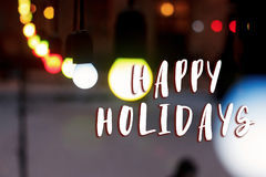 Happy holidays text sign on colorful retro garland lights bulbs. At street in european city at winter seasonal holidays. decorations outdoors. magic moments Stock Photos
