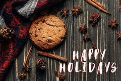 Happy holidays text sign on cookie anise cinnamon and pine cones. On wooden background, stylish rustic winter flat lay. space for text. cozy mood autumn Stock Images