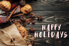 Happy holidays text sign on cookies cupcakes and spices on woode. N background, stylish rustic winter flat lay.  cozy mood autumn. seasonal holidays bakery Stock Photos