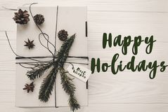 Happy holidays text sign, greeting card. stylish christmas rusti. C gift box flat lay. white present with green tree fir branch and pine cones anise top view on Royalty Free Stock Images