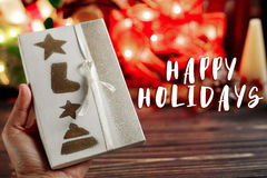 Happy holidays text sign on hand holding christmas wrapped prese. Nt box on background of warm garland lights on stylish black rustic wooden background. space Royalty Free Stock Photo