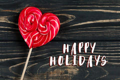 Happy holidays text sign on heart candy lollipop on stylish blac. K rustic wooden background. space for text. happy valentines day concept. holiday greeting card Royalty Free Stock Photography