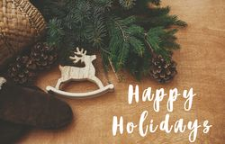 Free Happy Holidays Text Sign On Reindeer Toy, Gloves, Basket With Fir Branches And Cones On Rustic Wooden Background. Flat Lay. Zero Stock Image - 164238711