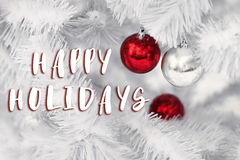 Happy holidays text sign on red and silver ornament balls on whi. Te christmas tree branches. space for text. greeting card. winter holidays concept wallpaper Royalty Free Stock Photography