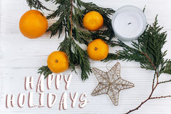 Happy holidays text sign on stylish christmas flat lay with gree. N branches and oranges and golden star on white rustic wooden background. seasonal greeting and Stock Images