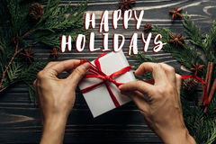 Happy holidays text sign on stylish christmas flat lay with hand. S wrapping present with red ribbon on rustic  wooden background with green branches. seasonal Stock Images
