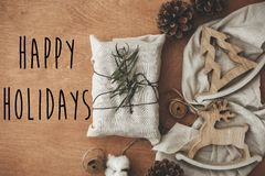 Happy Holidays text sign on stylish christmas rustic gift wrapped in linen fabric with green branch with pine cones, tree,reindeer. Seasonal greeting card royalty free stock images