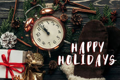 Happy holidays text sign on stylish vintage clock with almost tw. Elve hour and presents ornaments and branches on christmas rustic wooden background flat lay Stock Photo