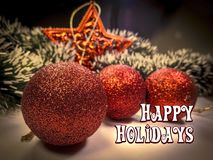 Happy Holidays text in white color on christmas tree ball and star toys and garlands background. Royalty Free Stock Photos