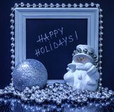 Happy holidays text in a white wooden frame with a snowman, silv. Er ball and beads Stock Image