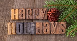 Happy Holidays Text. On a wooden surface with evergreen tree branch and pine cone Stock Photo