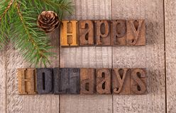 Happy Holidays Text. On a wooden surface with evergreen tree branch and pinecone Stock Photo