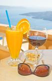 Happy holidays. Thirsty work ?. An image of a glass of fresh orange juice and a glass of red wine together with sunglasses and salted peanuts set on a table Stock Images