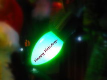 Happy Holidays on tree light. Happy Holidays in text graphics illustrated on illuminated Christmas tree light Royalty Free Stock Images