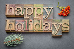 Happy Holidays in wood type. Happy Holidays banner or greeting card in letterpress wood type blocks against slate stone Royalty Free Stock Photography
