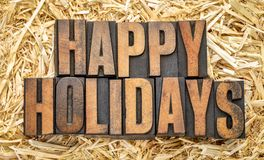 Happy Holidays in wood type. Happy Holidays banner or greeting card in vintage letterpress printing blocks against a straw bale stock photo