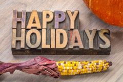 Happy Holidays in wood type. Happy Holidays banner or greeting card in vintage letterpress wood type with pumpkin and corn Stock Images