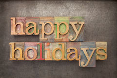 Happy holidays in wood type. Happy holidays - text in letterpress wood type against grunge metal background Stock Photography
