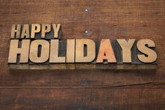 Happy holidays in wood type. Happy holidays  - text in vintage letterpress wood type blocks on a grunge wooden background Stock Photo